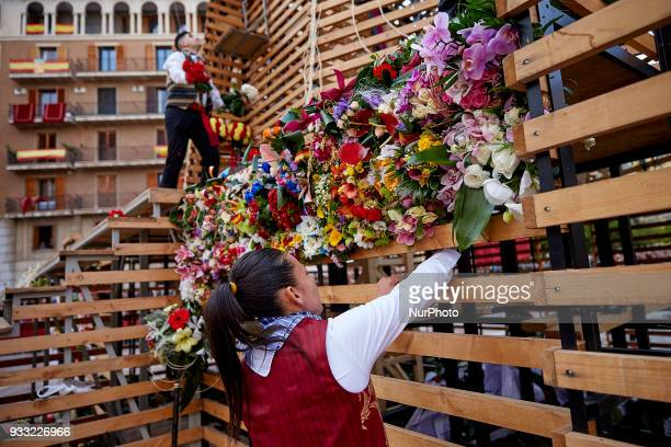A woman dressed in traditional costume works at the base of a large model of Saint Mary covered with flowers during Las Fallas Festival on March 17...