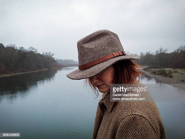 A woman dressed in tweed coat and hat, lost in thought while crossing a river on a cold misty morning walk
