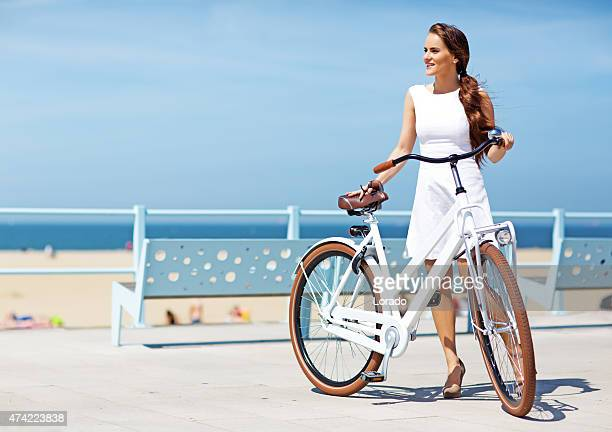 woman dressed in white  holding white bike walking near North sea