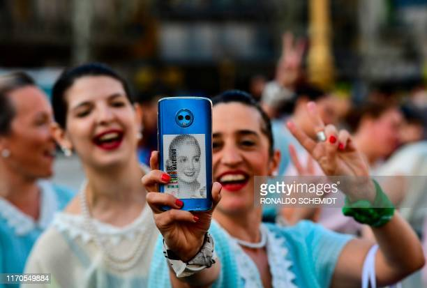 A woman dressed like former actress and first lady Eva Peron shows an image of Evita stuck on the back of her mobile phone as she marches to...