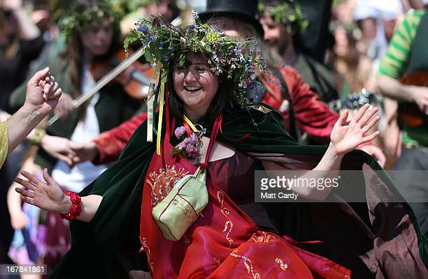 A woman dressed to represent the May Queen dances as she takes part in a Beltane May Day celebration in Glastonbury main street on May 1 2013 in...