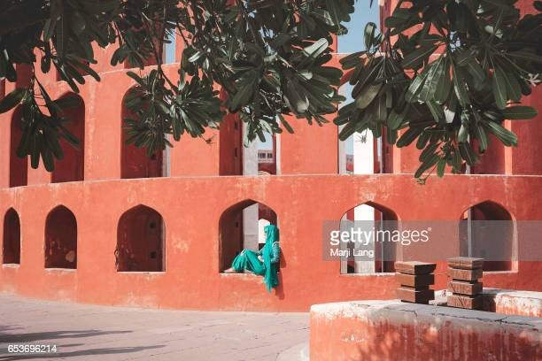 Woman dressed traditionally sitting in a window of the observatory in Jantar Mantar New Delhi India