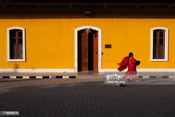 Woman dressed with a red sari walks by the colorful yellow painted French consulate of Pondicherry in a windy day. Pondicherry is an Indian Union...