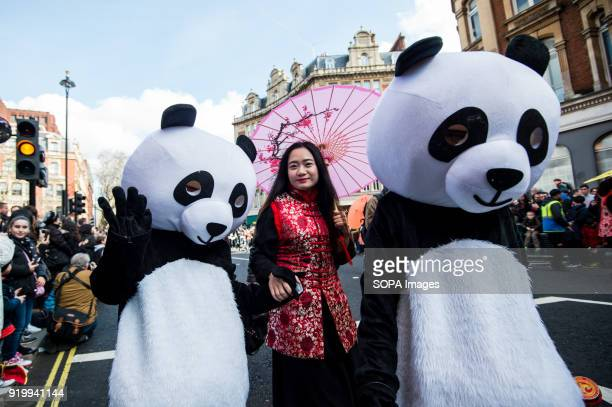 A woman dressed with traditional clothes seen posing for a picture near a panda character on the Chinatown streets during the Chinese New Year...
