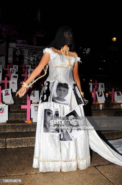 A woman dresses a a bride with pictures of victims perfroms during a protest of the 'Los Machos Nos Matan En Mexico' movement to demand justice for...