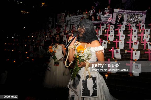 A woman dresses a a bride with pictures of victims speaks during a protest of the 'Los Machos Nos Matan En Mexico' movement to demand justice for the...