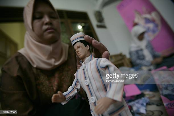 A woman dresses and assembles packaging of 'Arrosa' dolls on July 12 2007 in Depok West Java Indonesia In August 2005 the Arrosa Muslim doll factory...