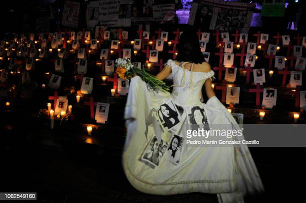 A woman dresses as a bride with pictures of victims performs during a protest of the 'Los Machos Nos Matan En Mexico' movement to demand justice for...