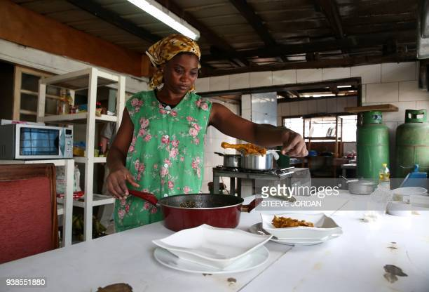 A woman dresses the plates with the chicken Nyembwe a chicken cooked in the juices of the palm fruits in the kitchen of a restaurant in Libreville on...