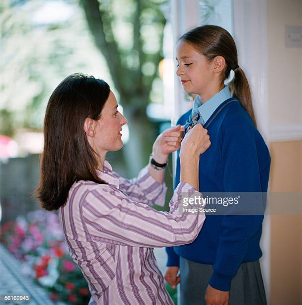 Woman dressing her daughter for school