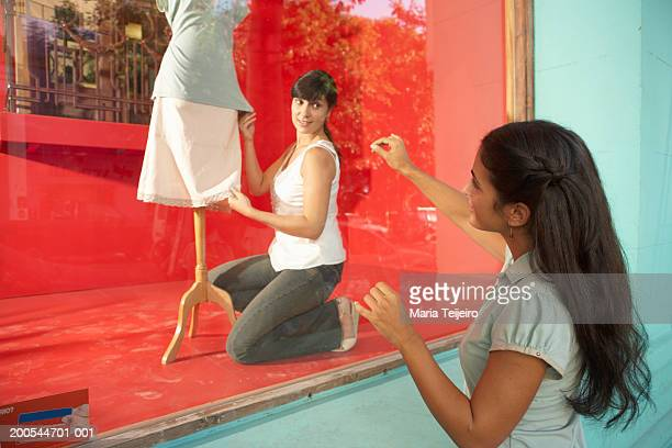 Woman dressing mannequin in shop window, young woman assisting