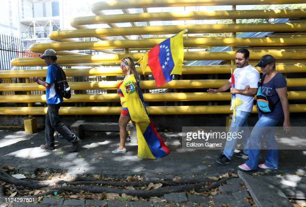 A woman dresss with a Venezuelan flag walks during a demonstration organized by Juan Guaidó President of the Venezuelan National Assembly at...