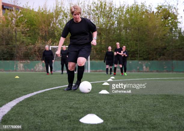 woman dribbles ball during football practice - menopossibilities stock pictures, royalty-free photos & images