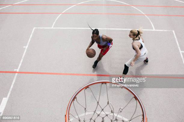 Woman dribling and playing  basketball with friend