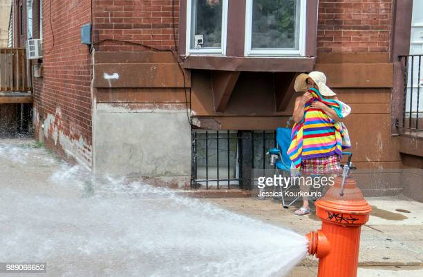 A woman dries off after cooling down in the spray of a fire hydrant during a heatwave on July 1 2018 in Philadelphia Pennsylvania An excessive heat...