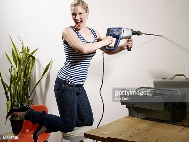 A woman drilling into a wall