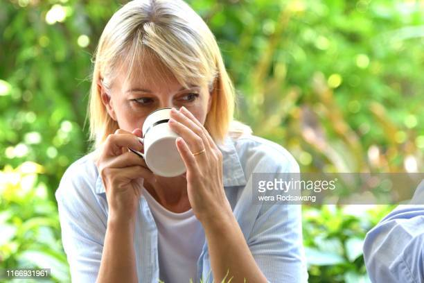 woman drink coffee in the garden - coffee drink stock pictures, royalty-free photos & images