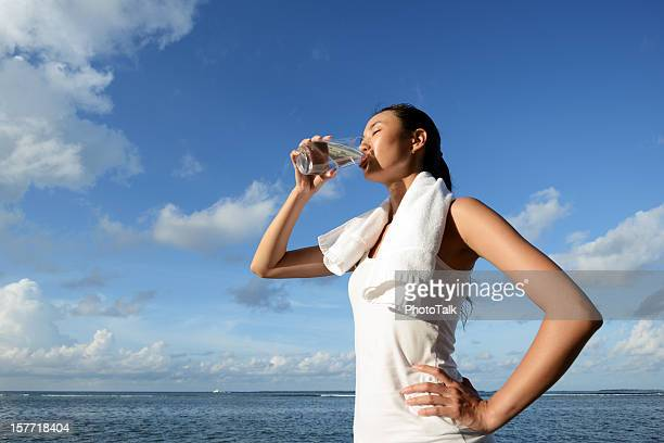 woman drink water after fitness - asian drink stock photos and pictures
