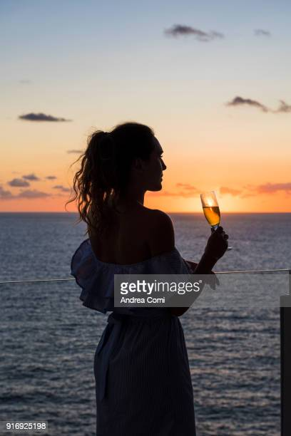 Woman drinking a cocktail at sunset