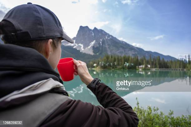 woman drinking a coffee cup at emerald lake in yoho national park, canada - british columbia stock pictures, royalty-free photos & images