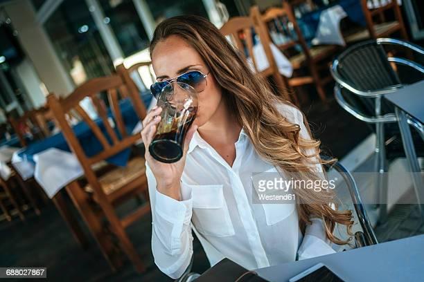 woman drinking a cola at a street cafe - coca cola imagens e fotografias de stock