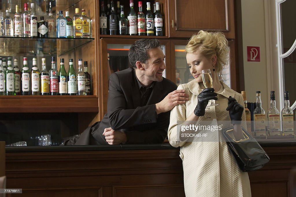 Woman drinking a glass of champagne, man touching her : Photo