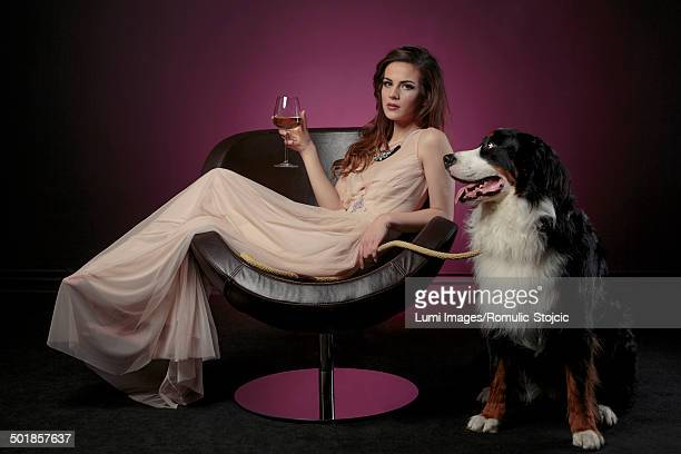 woman drinking a glass of wine alongside huge dog - evening gown stock photos and pictures