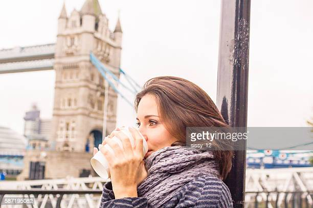 Woman drinking a hot coffee in autumn London