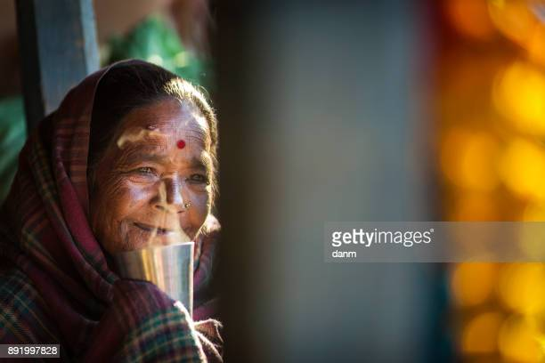 Woman drinking a hot tea in front of traditional house of Himalayan Village on November 19, 2017 in HIMALAYAN VILLAGE, Nepal