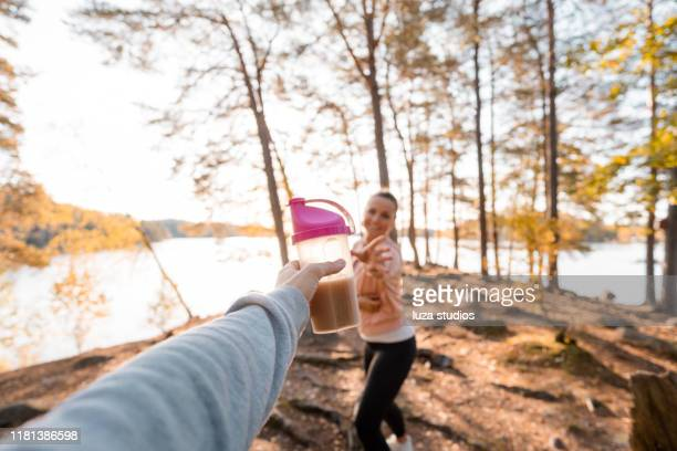 woman drinking a protein shake after outdoor workout - passing sport imagens e fotografias de stock