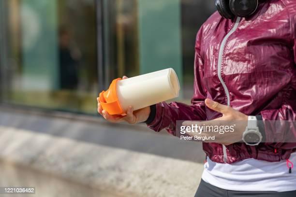 タンパク質シェイクを飲む女性 - たんぱく質 ストックフォトと画像