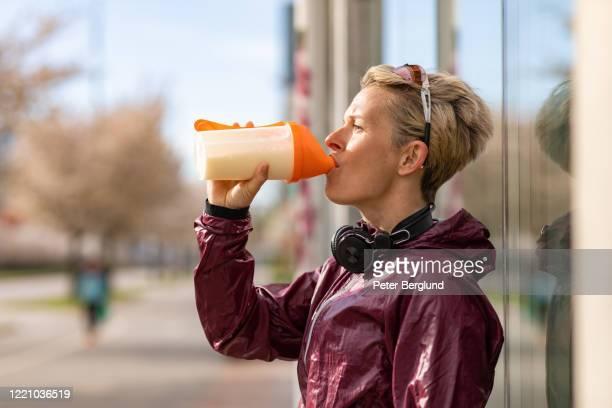 frau trinkt einen proteinshake - schütteln stock-fotos und bilder