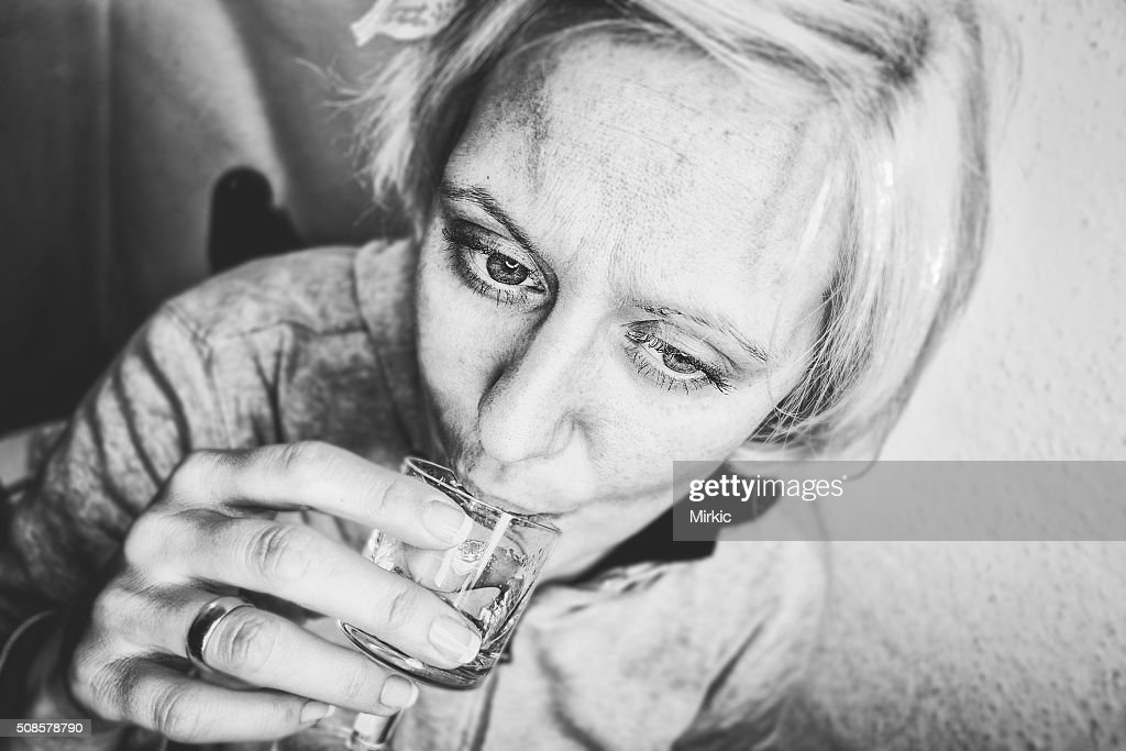 Woman drinking a short alcoholic drink : Stock Photo