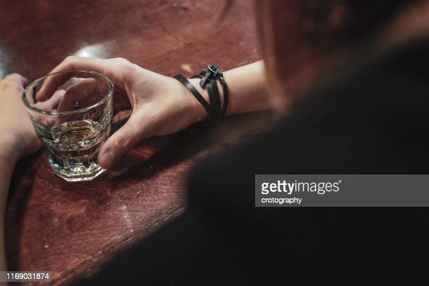 woman drinking a shot of whisky in a bar - drunk woman stock pictures, royalty-free photos & images