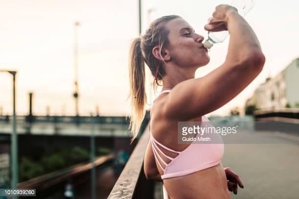 woman drinking after hard workout. - sport stock-fotos und bilder
