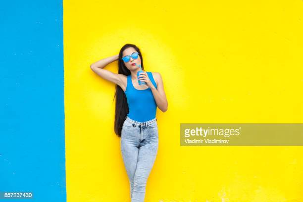 woman drinking and standing in front of colorful wall background - blue trousers stock pictures, royalty-free photos & images