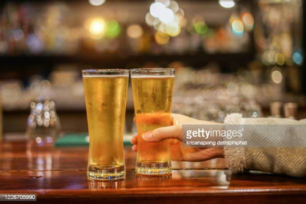 woman drinking and toasting beer at brewery bar restaurant,substance abuse - ラガービール ストックフォトと画像