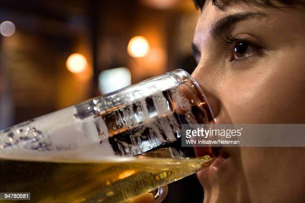 Woman drinking beer in a bar