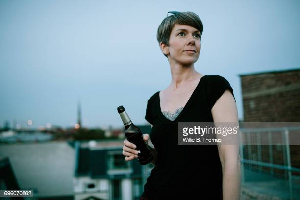 A Woman Drinking Beer On A Rooftop