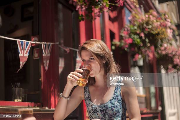 woman drinking beer while sitting outside pub during sunny day - pub stock pictures, royalty-free photos & images