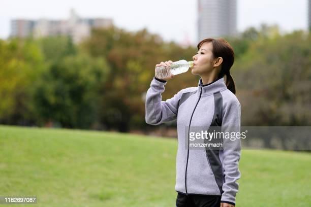 秋の公園で水のボトルを飲む女性 - チームジャージ ストックフォトと画像