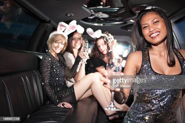 Woman drinking champagne in limo