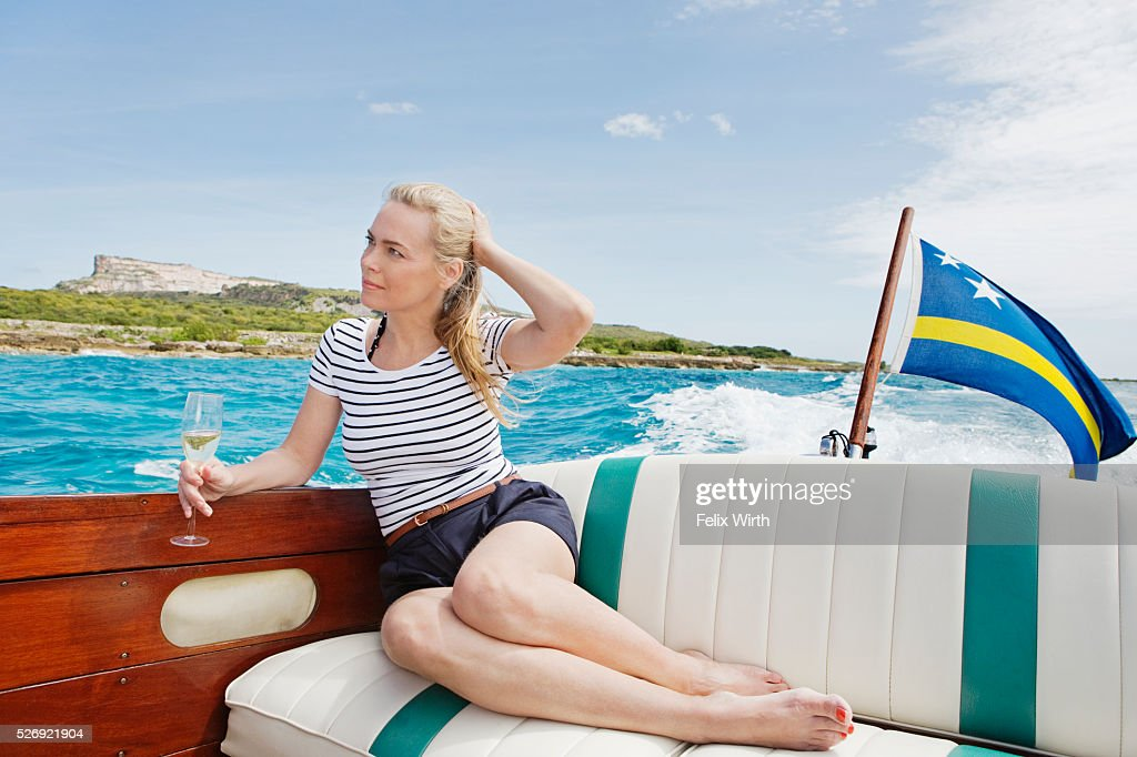 Woman drinking champagne on motorboat : Stockfoto