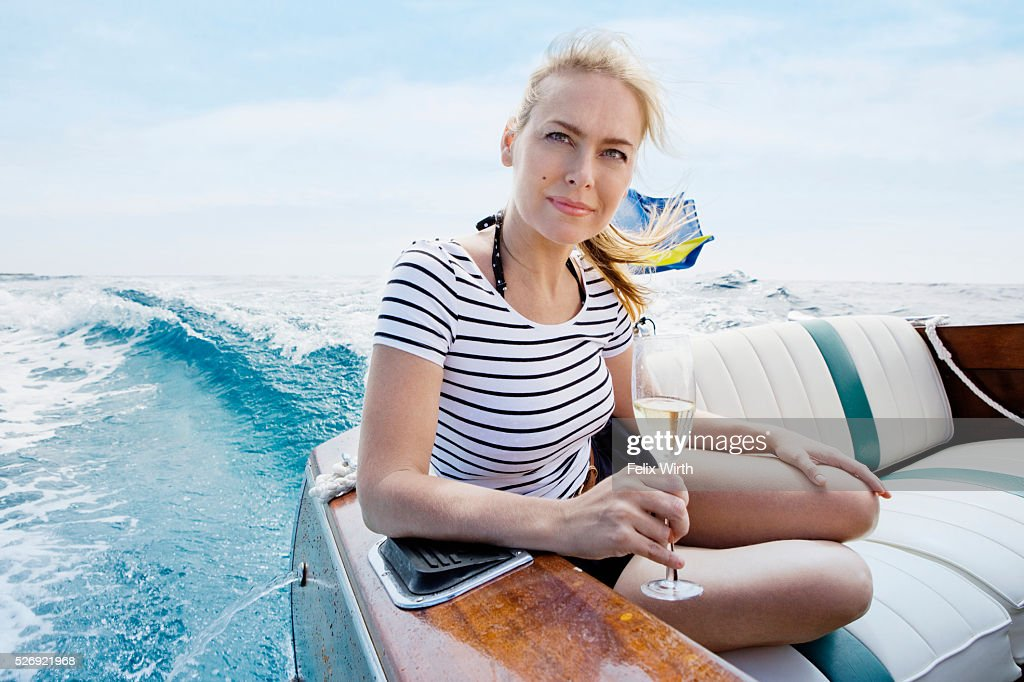Woman drinking champagne on motorboat : Foto de stock