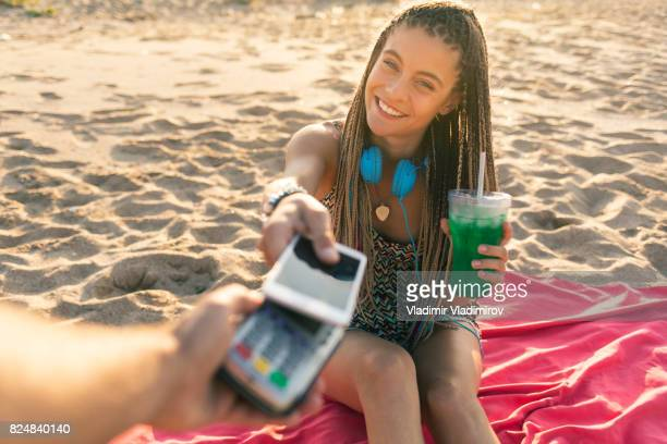 Woman drinking cocktail and using smart phone for mobile payment