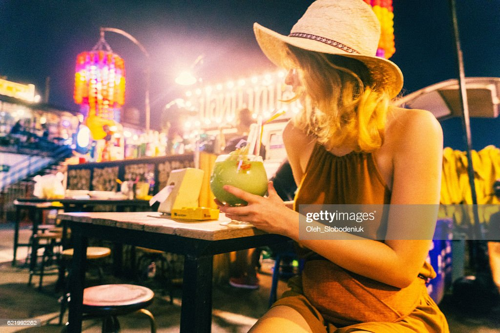 Woman drinking cocktail at night : Stock Photo