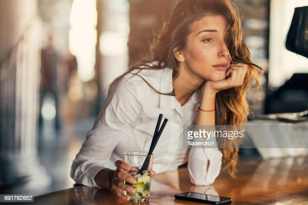 woman drinking cocktail in a bar - binge drinking stock photos and pictures