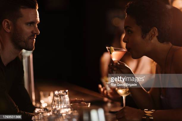 woman drinking cocktail while talking to smiling bartender in restaurant - voice stock pictures, royalty-free photos & images