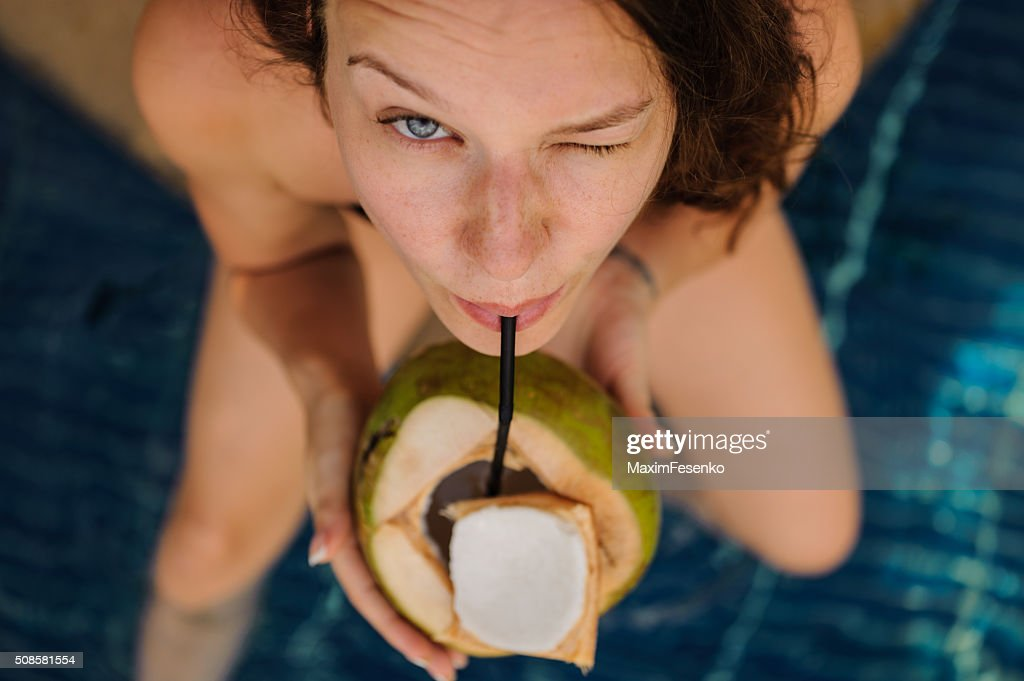 woman drinking coconut . Happy carefree freedom girl in summer day. : Stockfoto