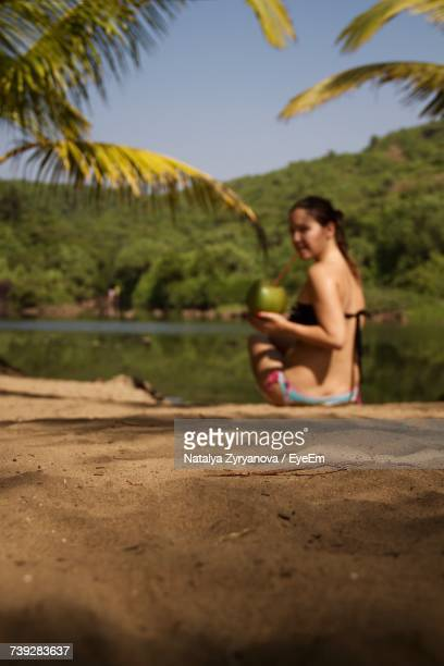 Woman Drinking Coconut Water While Sitting At Lakeshore